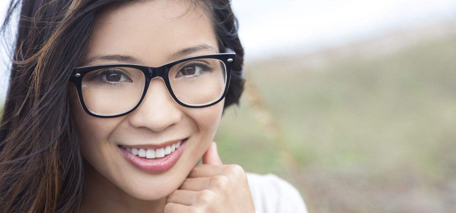 Smiling happy beautiful young Asian Chinese woman or girl wearing geek glasses outside
