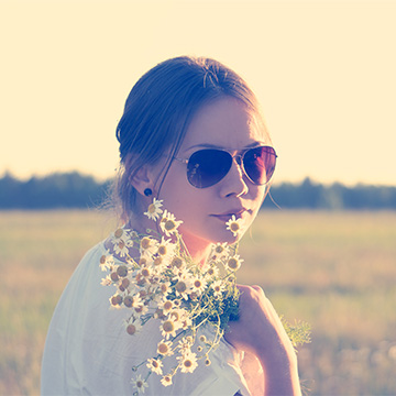 Young woman with flowers and sunglasses