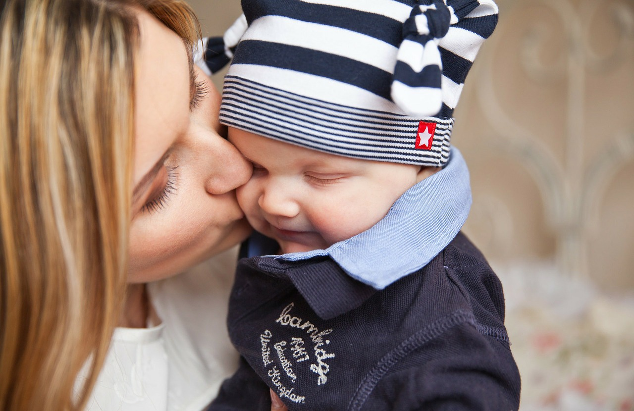 Mother kissing infant boy to prepare for eye doctor visit